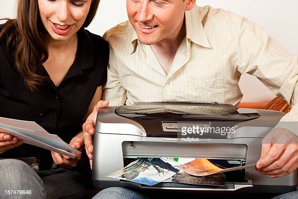 couple sitting on the couch printing photos