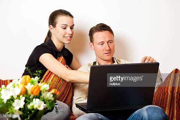 Coppia seduta sul divano con un computer portatile