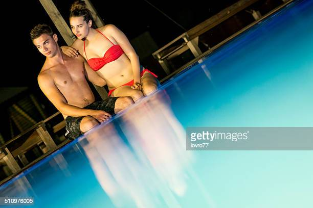 Couple sitting on the edge of swimming pool