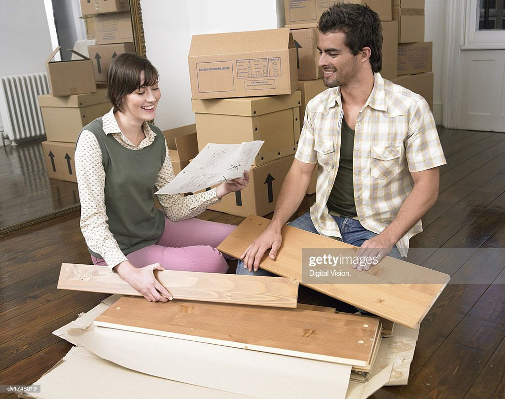 Couple Sitting On The Floor Of A Living Room Building Flat Pack Furniture Stock Photo