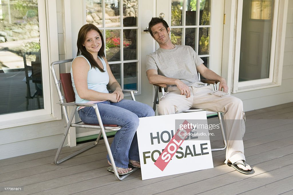 Couple sitting on the porch of their new home : Stock Photo