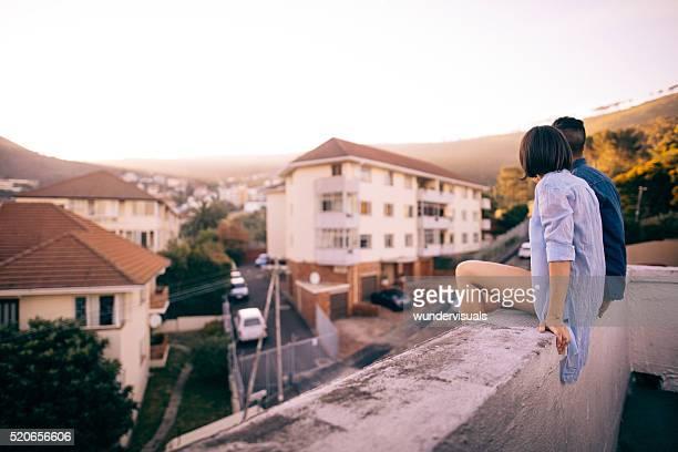Paar, sitzen auf dem Dach bietet einen Sonnenuntergang über der Stadt
