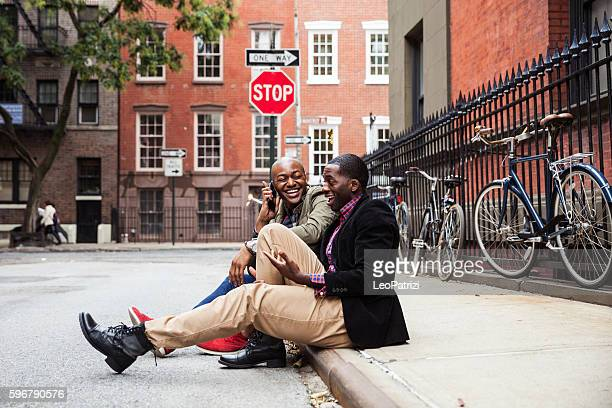 Couple sitting on the sidewalk in New York City
