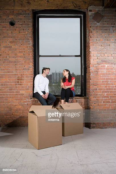 A couple sitting on the window sill with cardboard boxes
