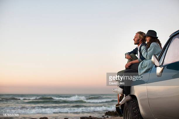 Couple sitting on truck looking at ocean view