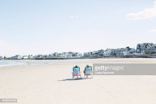 A couple sitting on two chairs on a deserted beach
