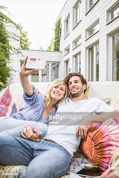 Couple sitting on vintage sofa in garden taking smartphone selfie