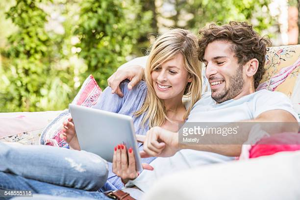 Couple sitting on vintage sofa in garden using digital tablet