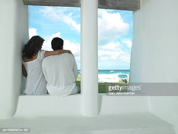 Couple sitting on window sill, looking over sea, rear view