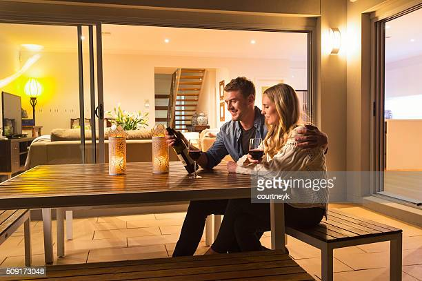 Couple sitting outside their home at night.