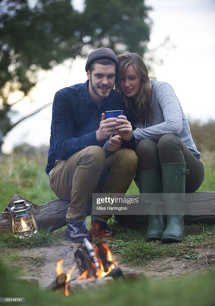 Couple sitting over campfire huddling together. : Stock Photo