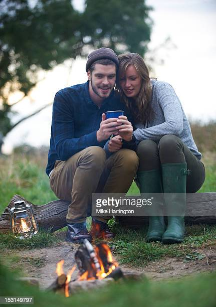 Couple sitting over campfire huddling together.