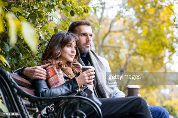Couple sitting relaxed at park with cup of coffee
