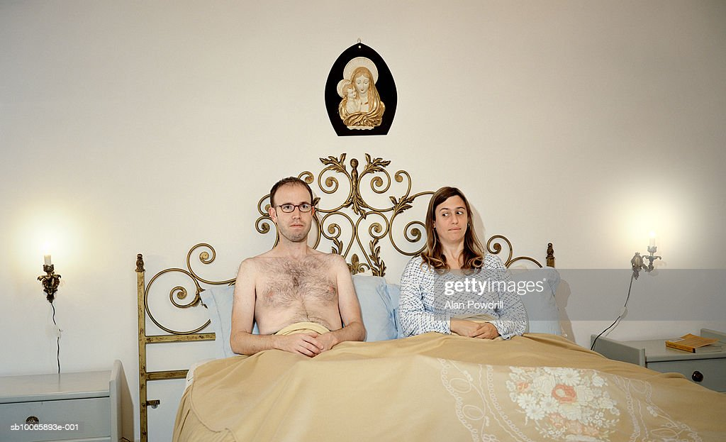 Couple sitting side by side in bed : Stock Photo