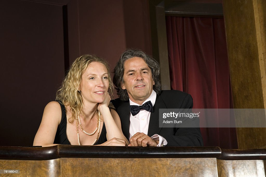 A couple sitting together in a theater box