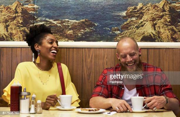 Couple sitting together in cafe laughing