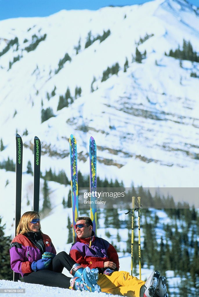 Couple sitting with backs against skis planted in snow,Colorado,USA