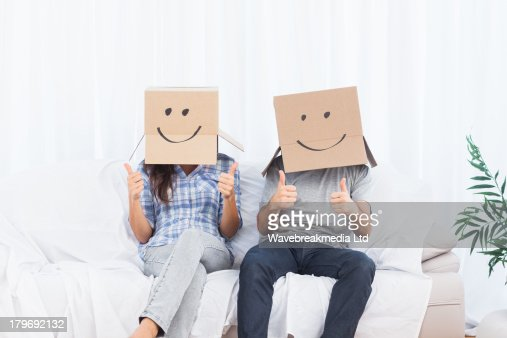 Couple sitting with cardboard boxes on head giving thumbs up : 스톡 사진