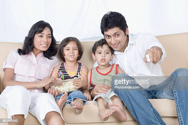 Couple sitting with their children on a couch