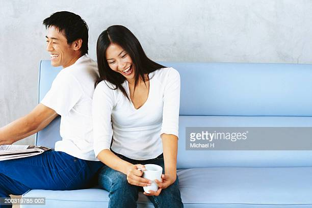Couple sitting, woman leaning on man's back