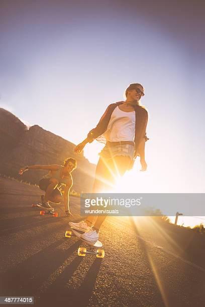 Couple skateboarding on road in sunset