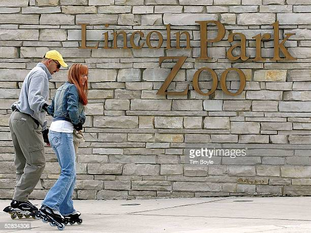 A couple skates toward an entrance to Lincoln Park Zoo May 16 2005 in Chicago Illinois Authorities are investigating the recent deaths at the zoo of...