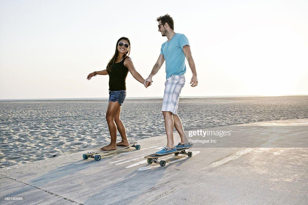 Couple skating on beach : Stock Photo
