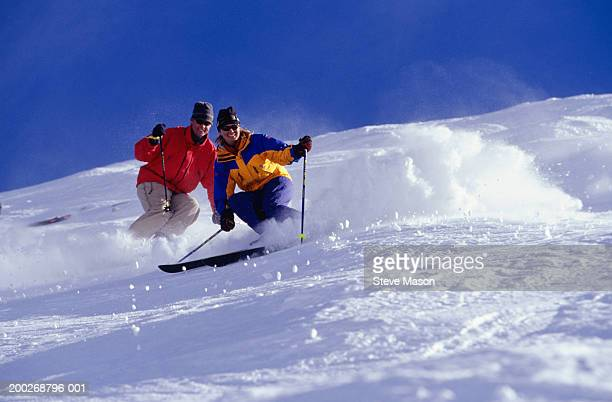 Couple skiing side by side down hill, low angle view