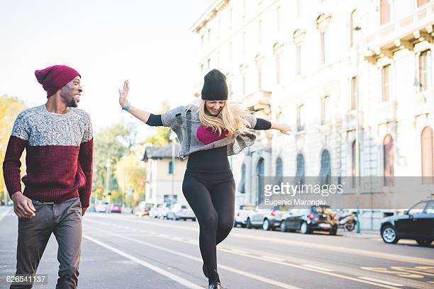 Couple skipping on street