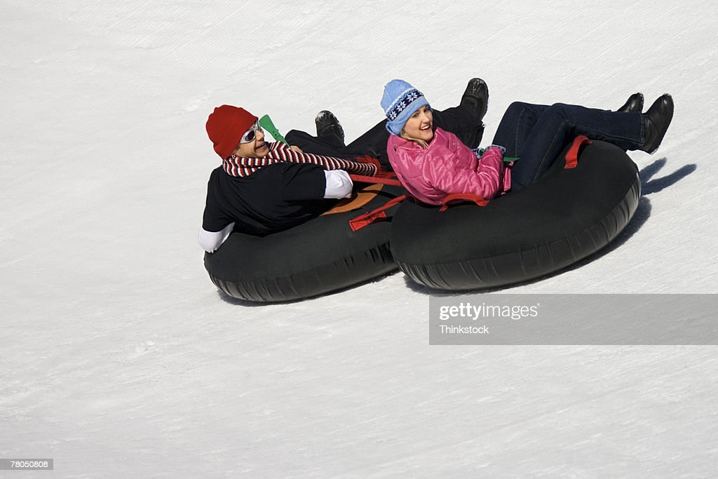 Couple sledding in inner tubes