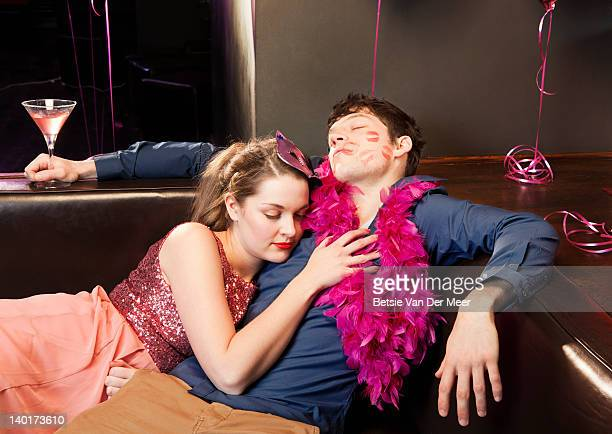 couple sleeping, exhausted at party.