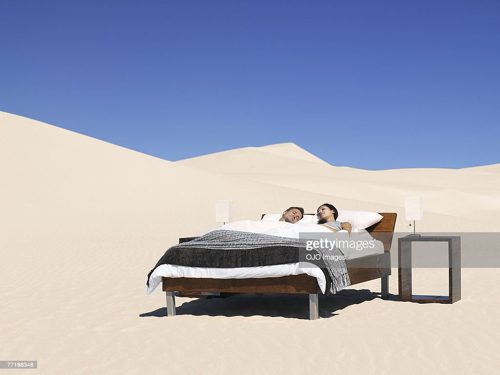 A couple sleeping in a bed outdoors : Stock Photo