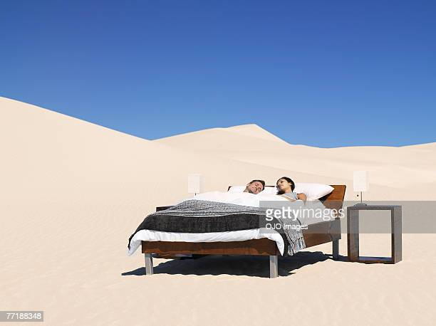 A couple sleeping in a bed outdoors