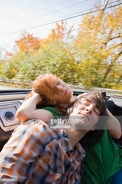 Couple sleeping in backseat of vintage convertible