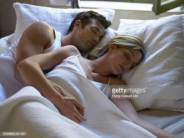 Couple sleeping in bed by open window