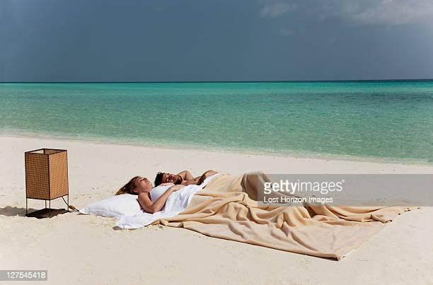Couple de dormir dans le lit sur la plage