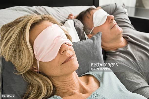Couple sleeping in bed wearing eye masks