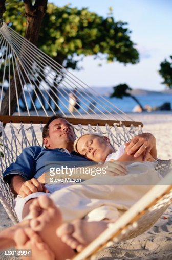 Couple sleeping in hammock at beach : Stock Photo