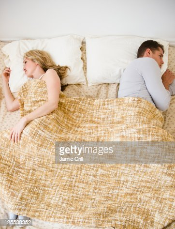 Couple sleeping on opposite sides of bed : Stock Photo