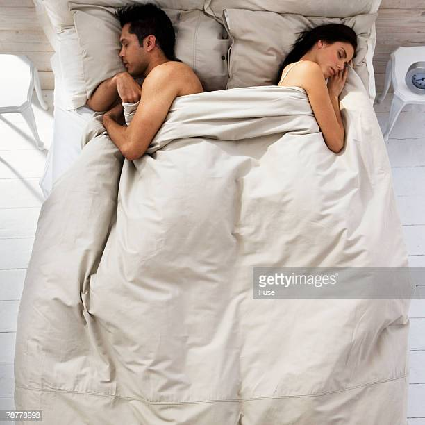 Couple Sleeping on Opposite Sides of Bed