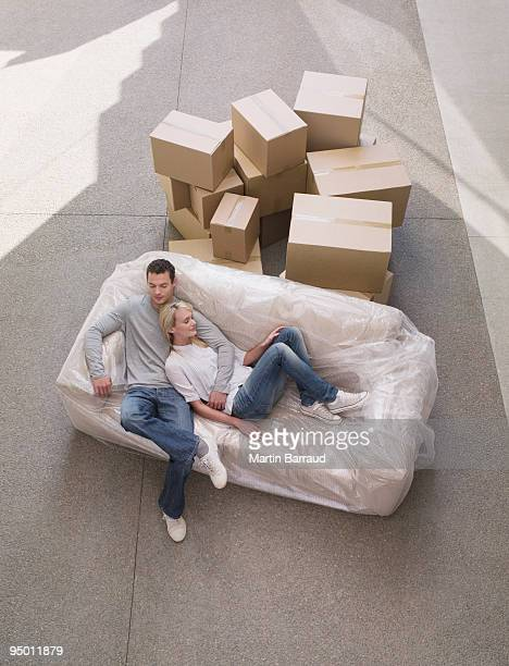 Couple sleeping on sofa wrapped in plastic