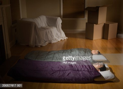 Couple sleeping side by side in sleeping bags on living for Is sleeping on the floor good