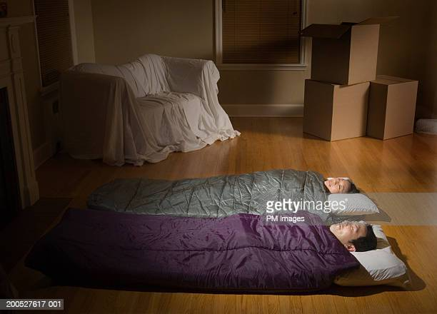 Couple Lying In Sleeping Bags Smiling In Living Room Photo – Sleeping in the Living Room