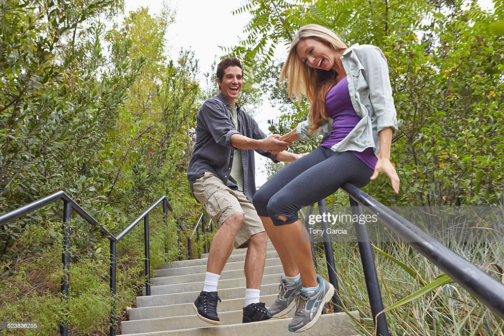 Couple sliding down step railing in forest