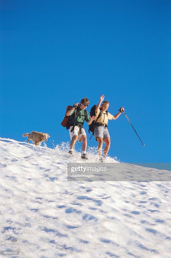 Couple sliding in snow : Stock Photo
