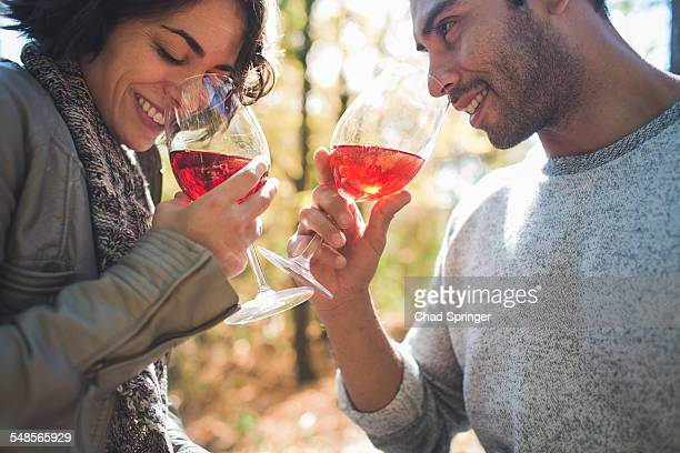Couple smelling aroma of rose wine in forest