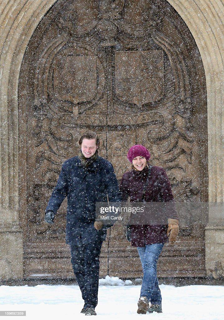 A couple smile as they walk into the snow in front of the west door of Bath Abbey on January 18, 2013 in Bath, England. Heavy snow is bringing widespread disruption to many parts of the UK.