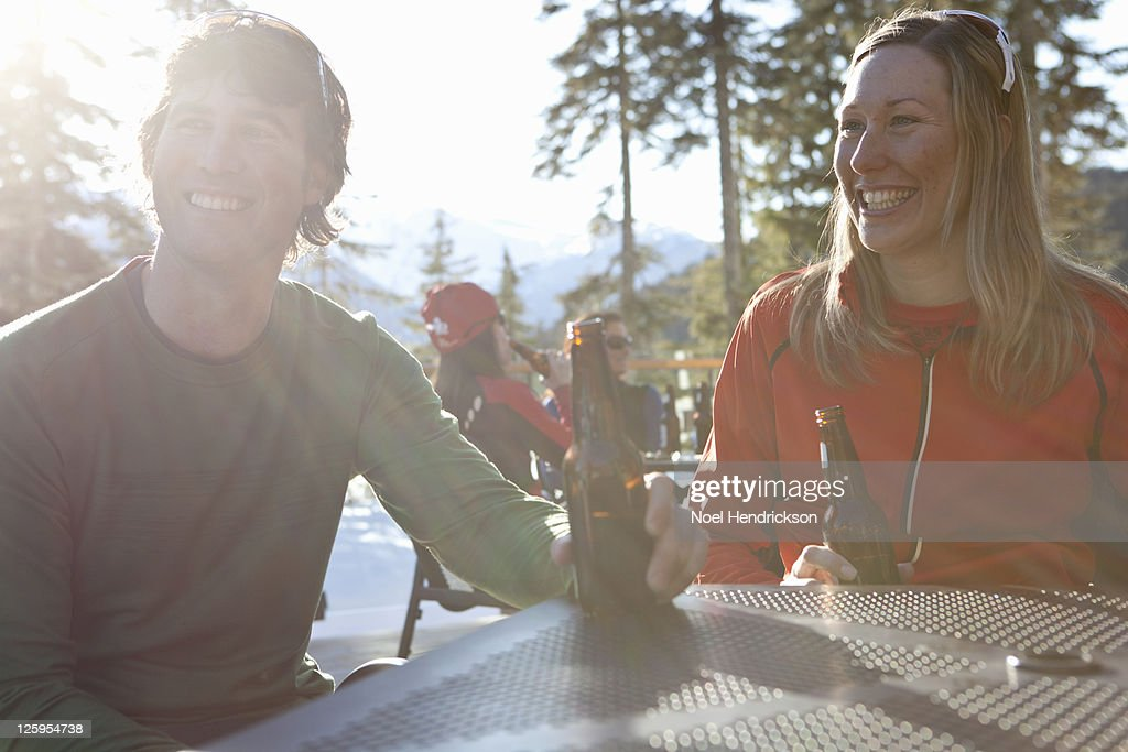 Couple smiles while drinking beer on patio : Stock Photo