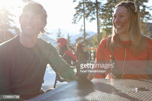 Couple smiles while drinking beer on patio