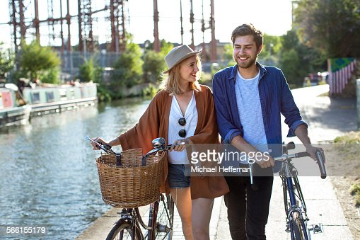 Couple smiling and walking along canal with bikes